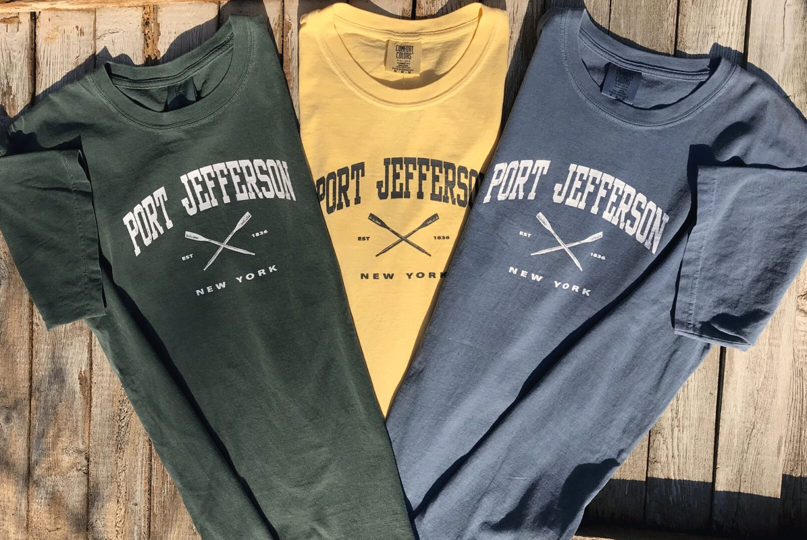 multi-colored shirts with Port Jefferson text on a wooden surface