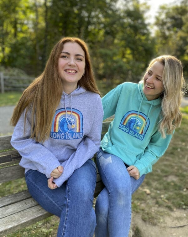 two girls wearing a rainbow hoodie on a bench