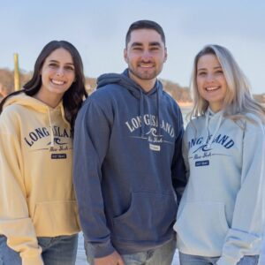 Three young adults wearing long island hoodies in yellow, steel blue and powder