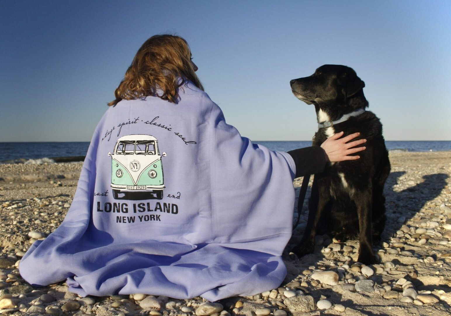 long island blanket drapped around a young woman with a dog